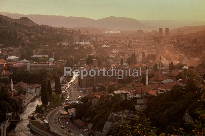 View of Sarajevo before the civil war from a nearby hill at dusk, showing the Miljacka river, the Ottoman Old Town in the middle distance and the 19th century Austro-Hungarian quarter behind. - Martin Mayer - 1990-09-07