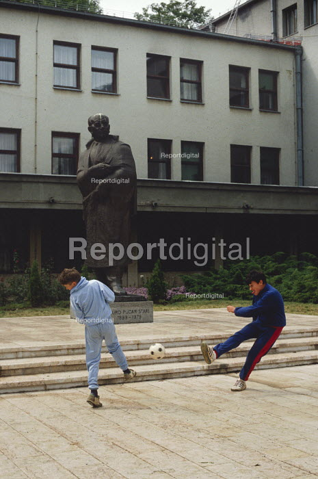 Boys play football outside the Communist Party offices in Sarajevo, after the break up of Yugoslavia. The Statue is of Durad Pucar, first President of the Peoples Republic of Bosnia and Herzegovina - Martin Mayer - 1990-09-07