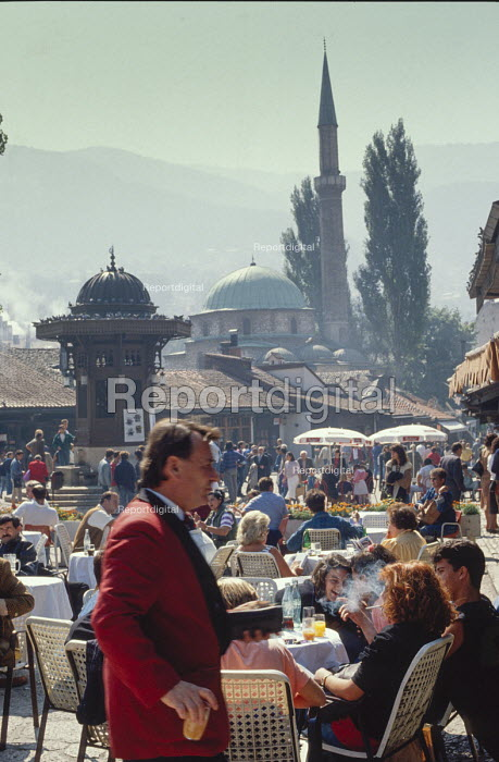 Cafe life in Sarajevo Old Town, Bosnia, with The Gazi Husrev-bey Mosque behind. - Martin Mayer - 1990-09-09