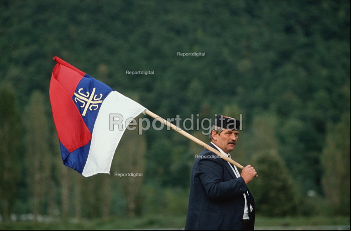 A supporter of the Bosnian Serb nationalist Serbian Democratic Party waves a Bosnian Serb flag while listening to a speech by their leader Radovan Karadzic at an election rally in Muslim majority town of Gorazde in eastern Bosnia. - Martin Mayer - 1990-09-09