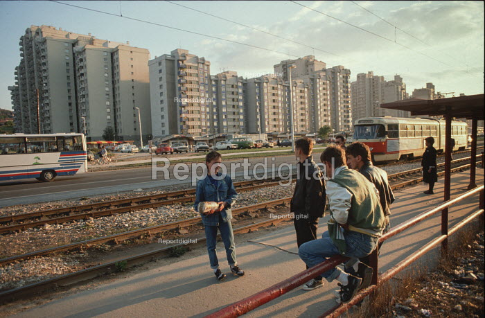 Young people wait for a tram near a high rise housing complex on the outskirts of Sarajevo, Bosnia - Martin Mayer - 1990-09-09