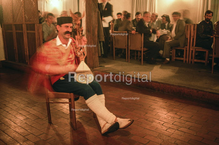 A musician in Serbian national costume plays a traditional Serbian song on a single stringed gusle instrument at a gathering after an election rally of the Bosnian Serb nationalist Serbian Democratic Party, SDP, Gorazde, eastern Bosnia 1990 - Martin Mayer - 1990-09-09