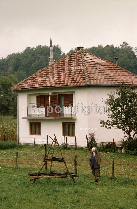 Elderly Muslim peasant woman outside her house in the Bosnian countryside - mosque in distance. - Martin Mayer - 1990-09-10