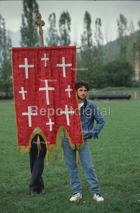 Denim clad supporter of the Bosnian Serb nationalist party - the Serb Democratic Party - with an Orthodox Christian Church banner listening to a speech by leader Radovan Karadzi, election rally in Gorazde, Eastern Bosnia. Serb nationalists tried unsuccessfully ethnic cleansing the town during the civil war. - Martin Mayer - 1990-09-10