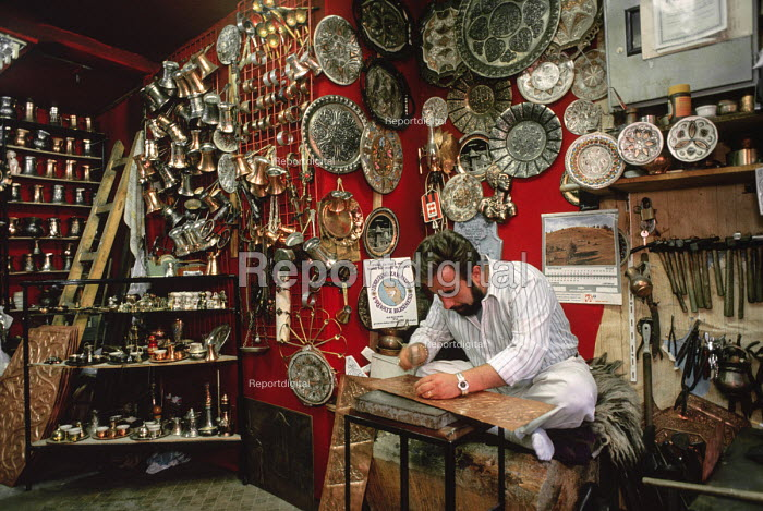 Maker of traditional copper and brassware at work in his shop in Sarajevo tourist district of Old Town, Bosnia. The sign behind him says Hand for Work and Peace - a hope that was later thwarted, Bosnia 1990 - Martin Mayer - 1990-09-10