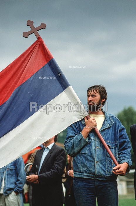 A denim clad, bearded supporter of the Bosnian Serb nationalist party Serbian Democratic Party waving a Serbian flag at an election rally in the Muslim majority town of Gorazde in Eastern Bosnia - Martin Mayer - 1990-09-12