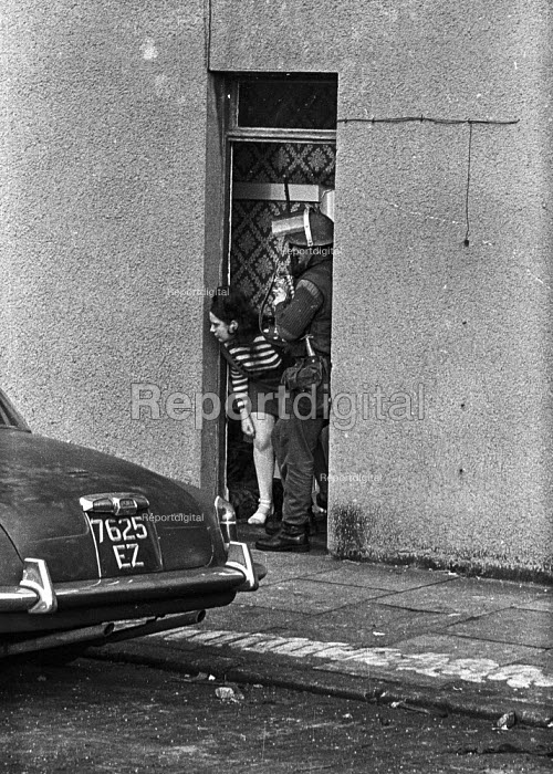 Young woman looking anxiously down the street in the Protestant Crumlin Road area, Belfast 1971 as a British soldier takes up position in her doorway after an incident when another soldier was shot - Martin Mayer - 1971-08-14