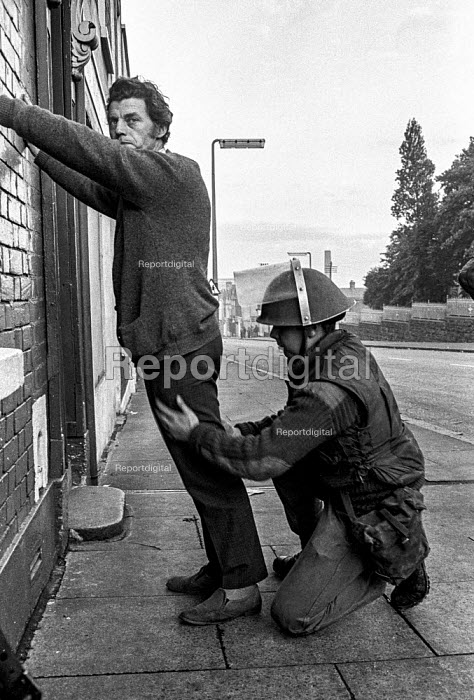British soldier in the Protestant Crumlin Road area, Belfast 1971 searching a man during an incident in whaich another soldier was shot, shortly after the announcement of internment without trial in Northern Ireland - Martin Mayer - 1971-08-17