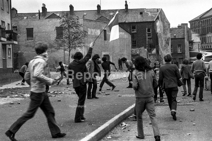 Stone throwing youths confronting British army, The Bogside, Derry, Northern Ireland, 1971 as one of their number waves the Irish tricolor flag, shortly after the introduction of internment without trial - Martin Mayer - 1971-08-16