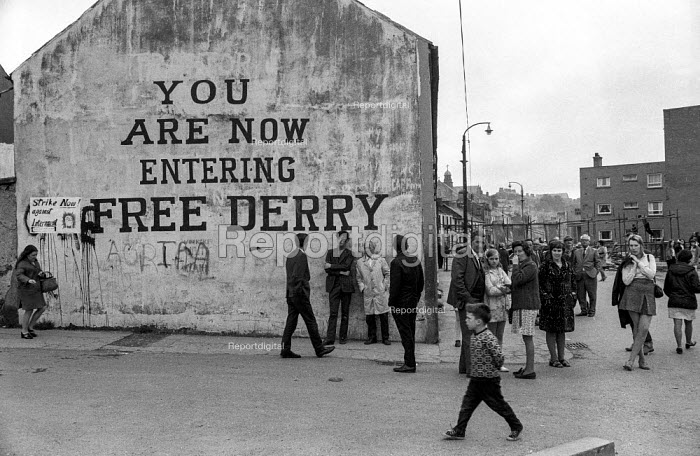 Derry residents gather near the famous Free Derry sign at the entrance to the no-go area of the Bogside, 1971 where armed IRA gunmen kept the army out after the introduction of internment without trial. The smaller poster says Strike Now against Internment! - Martin Mayer - 1971-08-16
