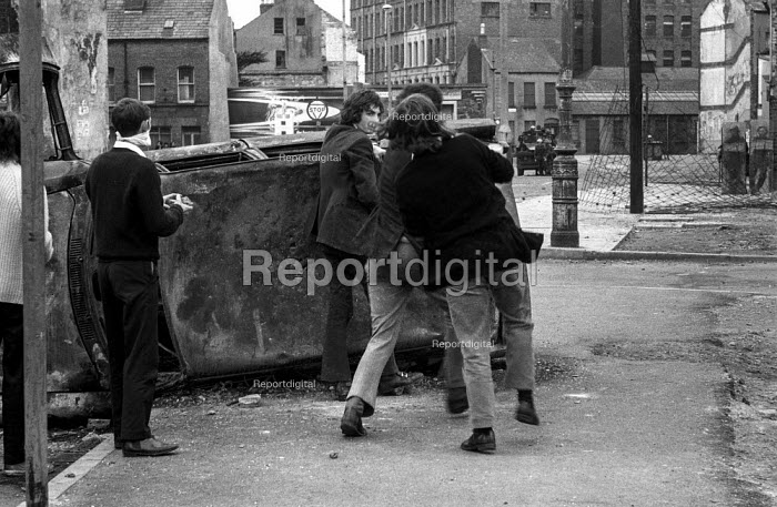 Stone throwing youths taunting British army from behind a burnt out car, The Bogside, Derry, Northern Ireland 1971 shortly after the introduction of internment without trial - Martin Mayer - 1971-08-16