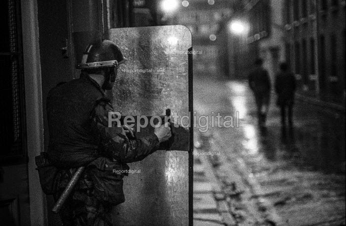 A british soldier behind a riot shield on the streets of Derry at night soon after the imposition of internment without trial - Martin Mayer - 1971-08-19