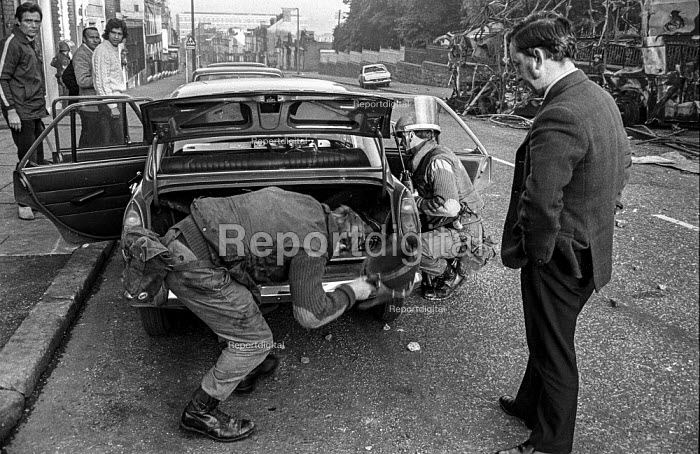 British soldiers searching a car in the Protestant Crumlin Road area of Belfast, during an incident in which a soldier was shot, soon after the introduction of internment without trial - Martin Mayer - 1971-08-17