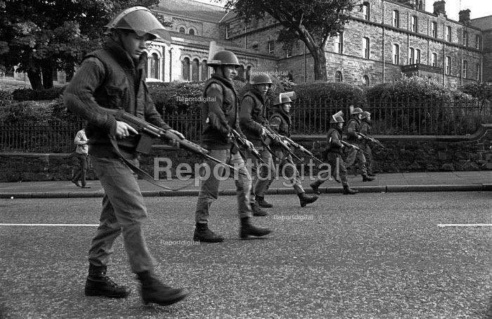 British soldiers patrol, Protestant Crumlin Road area, Belfast 1971 after an incident in which another soldier was shot, soon after the announcement of internment without trial in Northern Ireland - Martin Mayer - 1971-08-17