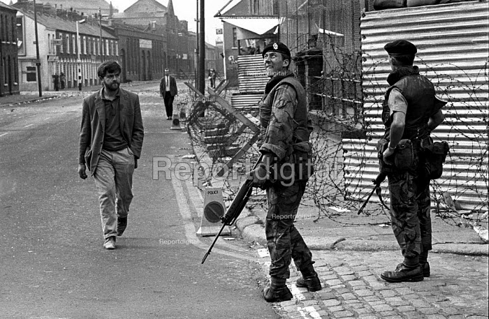 British soldier looking out anxiously for snipers in the Springfield Road area of Belfast on day 2 of internment without trial - Martin Mayer - 1971-08-10