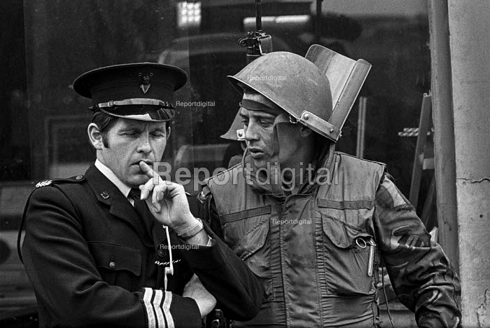 A British soldier and an RUC officer discuss what to do as protests at internment without trial spread in the prodominantly Catholic Short Strand area of East Belfast. - Martin Mayer - 1971-08-10