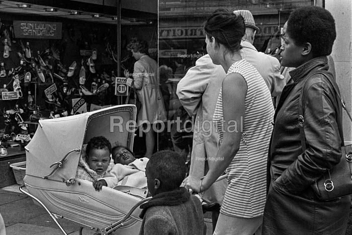 White childminder with 3 black children in Brixton High Street, summer 1970 - Martin Mayer - 1970-07-06
