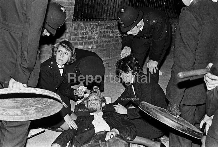 Notting Hill Carnival London 1976. Policeman injured in the riot, officers with dustbin lids for shields - Martin Mayer - 1976-08-30