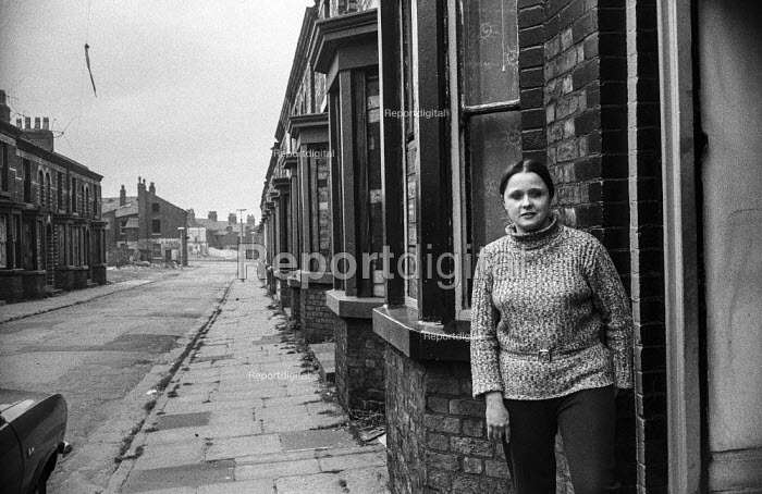 Carol Smith outside the house where she lives with her parents in Everton, Liverpool. They have been there a year waiting for the offer of a council house while the rest of the street has been abandoned for slum clearance. Someone has to be in all the time to prevent people breaking in. - Martin Mayer - 1972-04-26