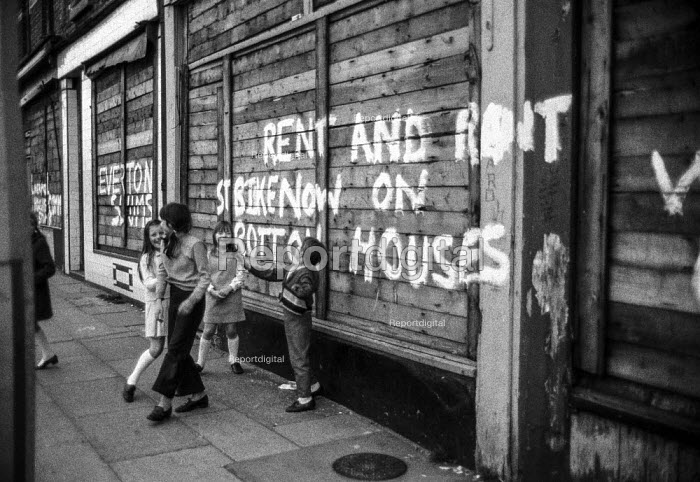 Children play in abandoned terraced streets, condemned as 'slums', next to slogans protesting at slum housing and calling for a rent and rates strike, Everton, Liverpool. - Martin Mayer - 1972-04-26