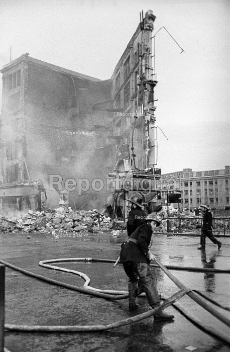 Firefighter hose down a fire at former Gardiners department store, Gardiner's Corner, Algate London. The store had closed a year before. The fire paved the way for new office blocks - Martin Mayer - 1972-05-22