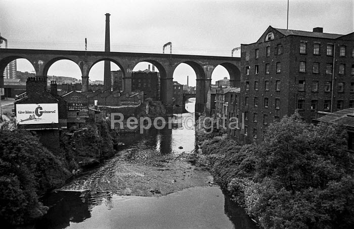 Stockport, Northern industrial landscape, river Mersey, mill and railway viaduct, once the biggest in the world, carrying the West Coast Main line, with a billboard advertising Give him Guinness and the Raja Indian restaurant 1970 - Martin Mayer - 1970-08-10