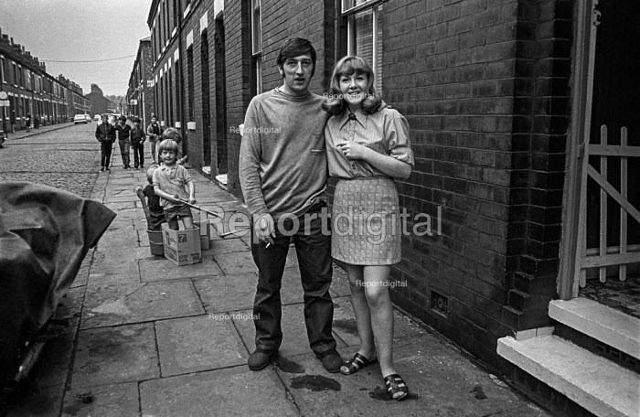 Young couple outside their terraced house in mill town Ashton-under-Lyne, Greater Manchester before setting off on traditional Wakes Week holiday - Martin Mayer - 1970-08-10