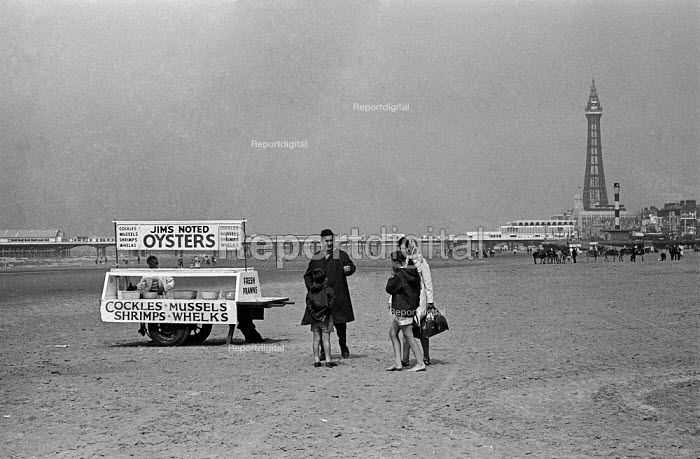 Family wonders whether to try some seafood from a cockle and mussel stall, Blackpool beach, Lancashire 1970 - Martin Mayer - 1970-08-09