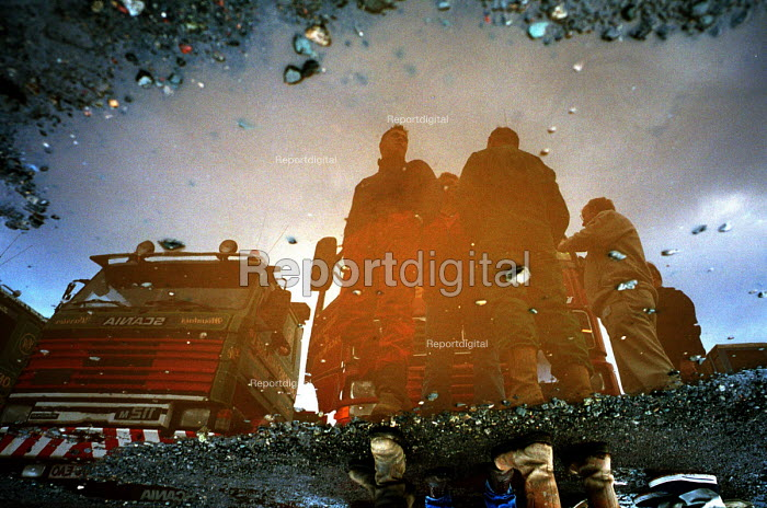 HGV lorry drivers relected in puddle. Birtley Truck stop, Birtley, Tyne and Wear, UK. - Mark Pinder - 2000-11-10
