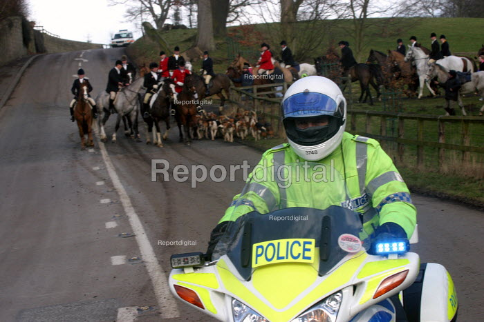 A motorcycle policeman escorts members of the Percy Hunt back to their stables the day after the hunting ban came into force in England and Wales. Alnwick, Northumberland, 19/2 2005. - Mark Pinder - 2005-02-19