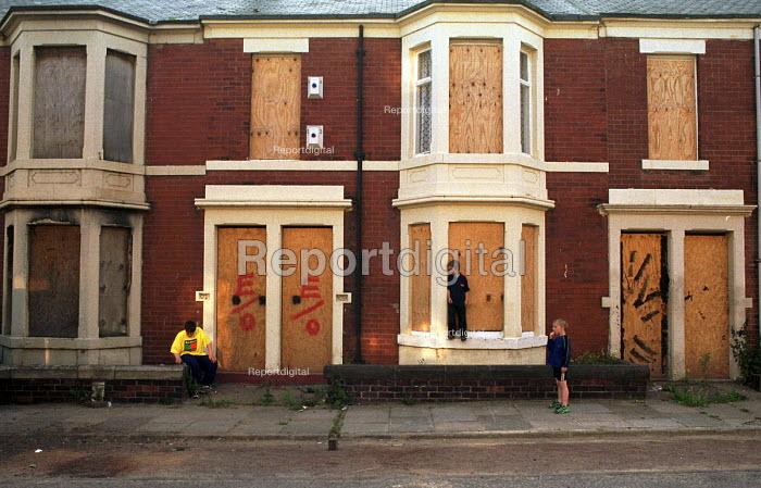Children playing in front of derelict and boarded up private flats and houses, North Benwell, Newcastle Upon Tyne. - Mark Pinder - 1999-06-25