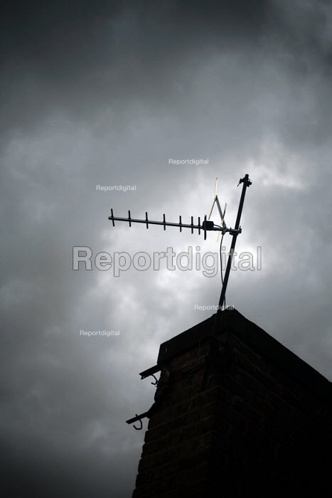 Television aerial on a roof silhouetted against a stormy sky on a chimney. North Shields, Tyne and Wear - Mark Pinder - 2009-07-24