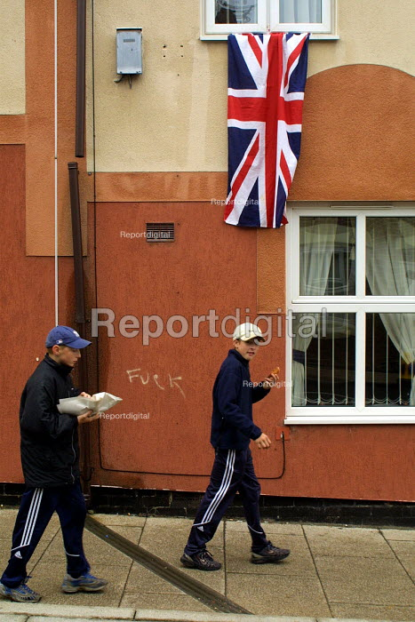 Two boys walk past a Union Jack draped from a house in Easington Colliery, Co Durham on the day of the Queens visit to the former mining town.The graffiti on the wall reads fuck - Mark Pinder - 2002-05-08