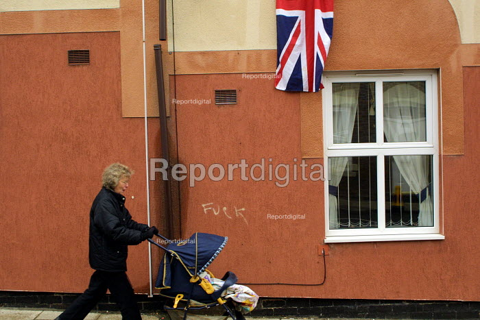 A woman pushes a pram past a Union Jack draped from a house in Easington Colliery, Co Durham on the day of the Queens visit to the former mining town.The graffiti on the wall reads fuck - Mark Pinder - 2002-05-08