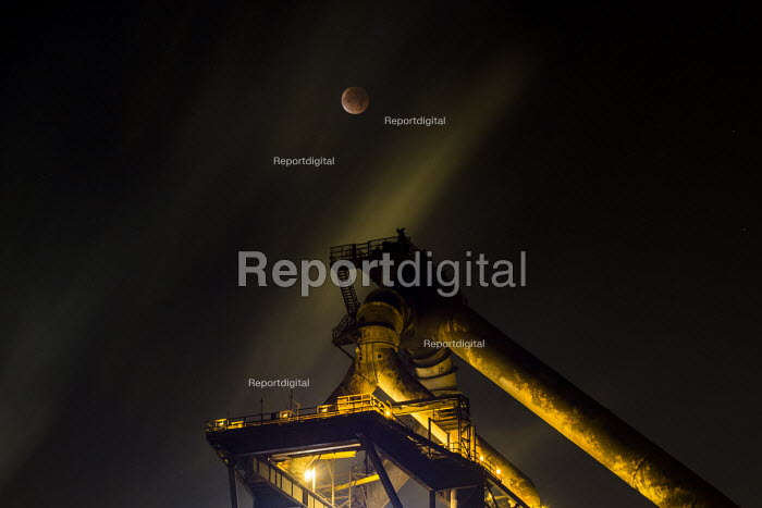 Lunar eclipse over the SSI Redcar steelworks blast furnace. SSI have announced the plant will be mothballed, with the loss of 1,700 jobs.