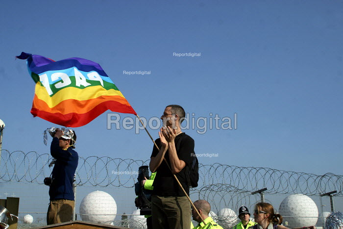 A protestor with a peace flag beside the perimeter fence at the Foil the Base event. Menwith Hill listening base, North Yorkshire. 22/3 2003. - Mark Pinder - 2003-03-22