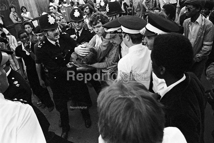 Notting Hill Carnival 1977. Person injured in the riots being rushed to an ambulance - Peter Arkell - 1977-08-28