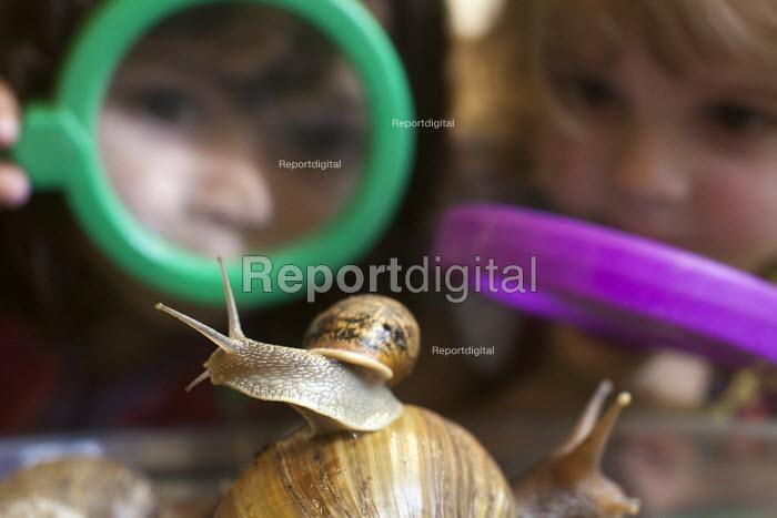 Girls play with giant snails, Norland Nursery, Bath. - Paul Box - 2012-06-27