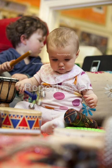 A boy plays a drum with a baby girl, Norland Nursery, Bath. - Paul Box - 2012-06-27