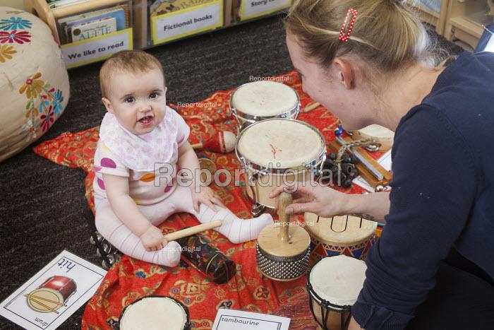 A baby plays a drum with a nursery worker, Norland Nursery, Bath. - Paul Box - 2012-06-27
