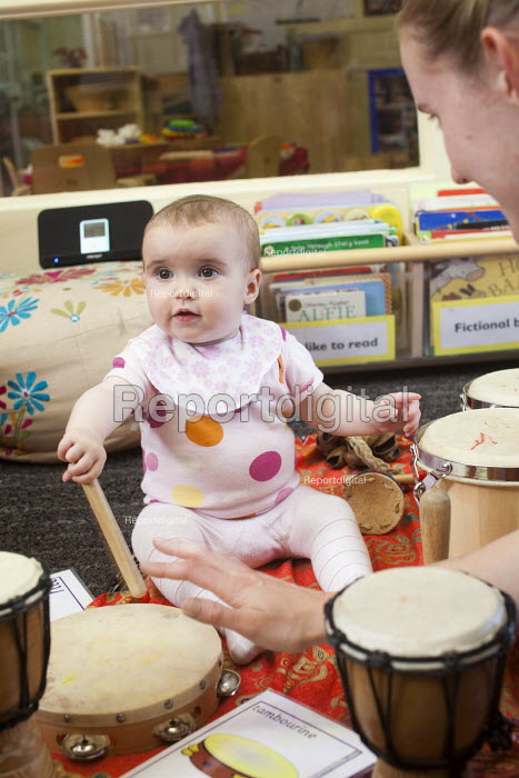 A baby playing a drum with a nursery worker, Norland Nursery, Bath. - Paul Box - 2012-06-27