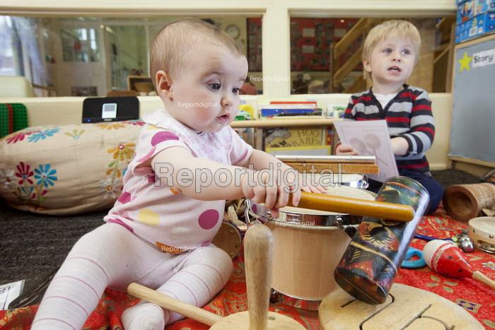 A baby plays a drum with an older boy, Norland Nursery, Bath. - Paul Box - 2012-06-27