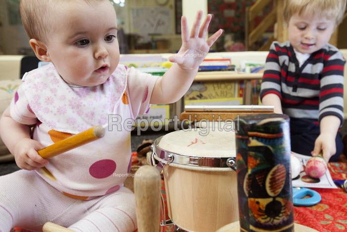 A baby playng a drum with an older boy, Norland Nursery, Bath. - Paul Box - 2012-06-27