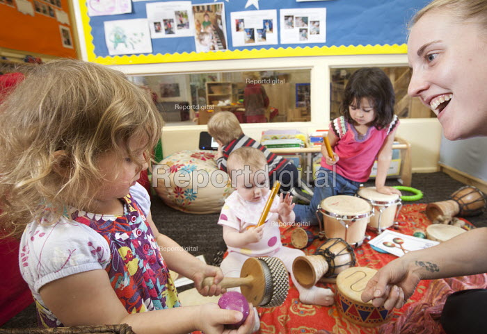 A young girl playsing a drum with older girls and a nursery worker, Norland Nursery, Bath. - Paul Box - 2012-06-27