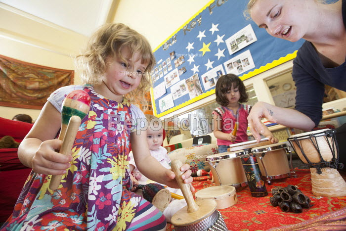 A young girl playsing a drum withan older girl and a nursery worker, Norland Nursery, Bath. - Paul Box - 2012-06-27