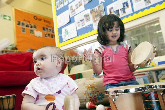 A young girl playsing a drum withan older girl, Norland Nursery, Bath. - Paul Box - 2012-06-27