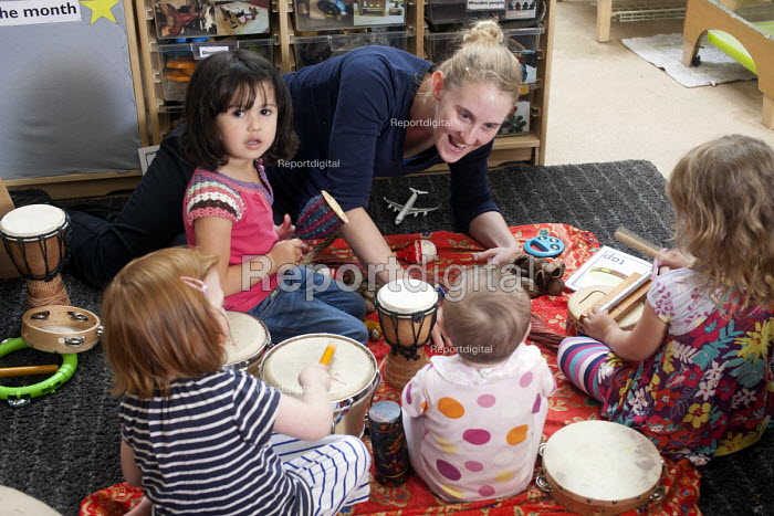 A young girl playing a drum with older girls and a nursery worker, Norland Nursery, Bath. - Paul Box - 2012-06-27