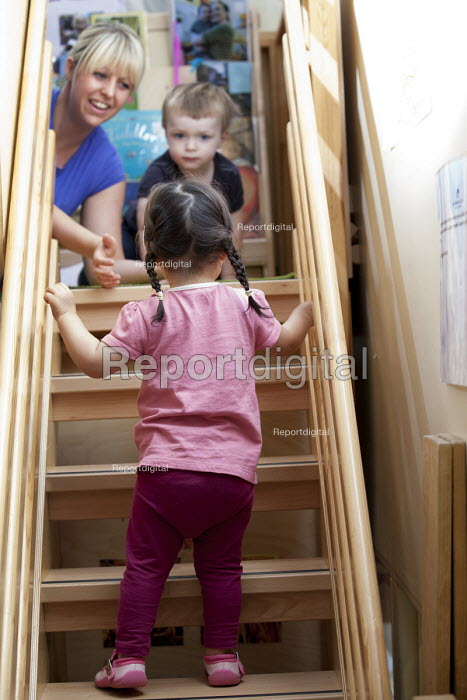 A young girl climbing the stairs with encouragement from a nursery worker, Norland Nursery, Bath. - Paul Box - 2012-06-27