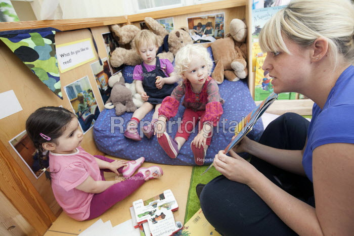 Young girls reading with a nursery worker, Norland Nursery, Bath. - Paul Box - 2012-06-27
