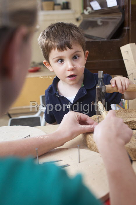A young boy using a hammer and nails with encouragement from a nursery worker. Norland Nursery, Bath. - Paul Box - 2012-06-27